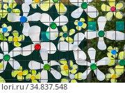 Decoration of multi-colored plastic bottles on a mesh metal fence. Стоковое фото, фотограф Валерий Смирнов / Фотобанк Лори