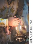 Orthodox Christian rite of baptism of a child. Baptism of the Child. Christianity. Bathing a child. Orthodox cross. Orthodox Church. Стоковое фото, фотограф Nataliia Zhekova / Фотобанк Лори