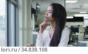 Thoughtful woman rubbing her chin and smiling in office. Стоковое видео, агентство Wavebreak Media / Фотобанк Лори