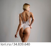 Rear view of blonde with perfect body posing in bodysuit. Стоковое фото, фотограф Zoonar.com/Andrey Guryanov / easy Fotostock / Фотобанк Лори