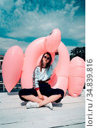 Young beautiful girl posing on the pier with an inflatable flamingo. Стоковое фото, фотограф Zoonar.com/Oleksii Hrecheniuk / easy Fotostock / Фотобанк Лори