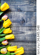 Yellow tulips lie on old wooden table background. Women's Day Concept. Стоковое фото, фотограф Анна Гучек / Фотобанк Лори