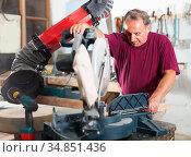 Carpenter cutting a wooden workpiece on an electical circular saw. Стоковое фото, фотограф Яков Филимонов / Фотобанк Лори
