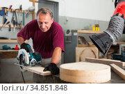 Worker cutting wooden workpiece on an hand electical circular saw. Стоковое фото, фотограф Яков Филимонов / Фотобанк Лори