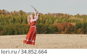 Feisty woman in red dress training on the field - trains with a sword and ending up posing. Стоковое видео, видеограф Константин Шишкин / Фотобанк Лори