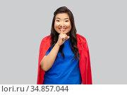 asian woman in superhero cape making hush gesture. Стоковое фото, фотограф Syda Productions / Фотобанк Лори