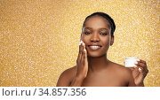 smiling african american woman with moisturizer. Стоковое фото, фотограф Syda Productions / Фотобанк Лори