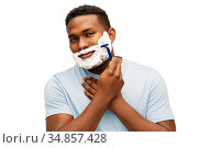 smiling african man shaving beard with razor blade. Стоковое фото, фотограф Syda Productions / Фотобанк Лори