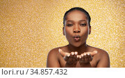 african woman blowing something off her hands. Стоковое фото, фотограф Syda Productions / Фотобанк Лори