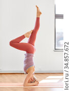 woman doing supported headstand at yoga studio. Стоковое фото, фотограф Syda Productions / Фотобанк Лори