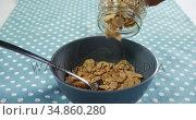 Hands spilling wheat corn flakes into bowl 4k. Стоковое видео, агентство Wavebreak Media / Фотобанк Лори