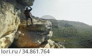 Male hiker walking with backpack near a cave 4k. Стоковое видео, агентство Wavebreak Media / Фотобанк Лори