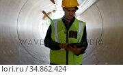 Male worker using digital tablet inside a concrete tunnel 4k. Стоковое видео, агентство Wavebreak Media / Фотобанк Лори