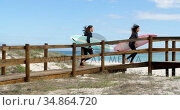 Couple running with surf board 4k. Стоковое видео, агентство Wavebreak Media / Фотобанк Лори