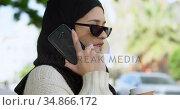 Woman in hijab talking on mobile phone while having coffee 4k. Стоковое видео, агентство Wavebreak Media / Фотобанк Лори