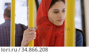 Woman in hijab standing while travelling in the bus 4k. Стоковое видео, агентство Wavebreak Media / Фотобанк Лори