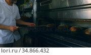 Male chef removing bread from oven 4k. Стоковое видео, агентство Wavebreak Media / Фотобанк Лори