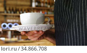 Male waiter holding a coffee cup in cafe 4k. Стоковое видео, агентство Wavebreak Media / Фотобанк Лори