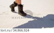 Woman in boots walking in the desert on a sunny day 4k. Стоковое видео, агентство Wavebreak Media / Фотобанк Лори