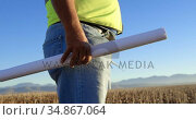 Male engineer standing with blueprint in the wind farm 4k. Стоковое видео, агентство Wavebreak Media / Фотобанк Лори