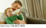 Boy in fathers lap drinking milk on sofa 4k. Стоковое видео, агентство Wavebreak Media / Фотобанк Лори