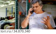Male mechanic talking on mobile phone 4k. Стоковое видео, агентство Wavebreak Media / Фотобанк Лори