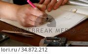 Female jewelry designer drawing sketch on register 4k. Стоковое видео, агентство Wavebreak Media / Фотобанк Лори