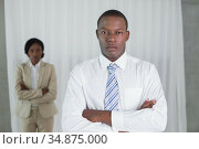 Stern businessman looking at camera with colleague behind. Стоковое фото, агентство Wavebreak Media / Фотобанк Лори