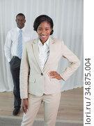Happy businesswoman looking at camera with colleague behind. Стоковое фото, агентство Wavebreak Media / Фотобанк Лори