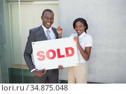 Estate agent and buyer holding sold sign and smiling at camera. Стоковое фото, агентство Wavebreak Media / Фотобанк Лори