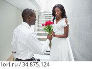 Man offering red roses to his beautiful girlfriend. Стоковое фото, агентство Wavebreak Media / Фотобанк Лори