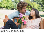 Cute young couple relaxing on park bench together with man offering flowers. Стоковое фото, агентство Wavebreak Media / Фотобанк Лори