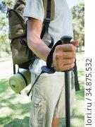 Young man on a hike walking with pole. Стоковое фото, агентство Wavebreak Media / Фотобанк Лори