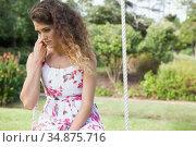 Upset woman sitting on a swing in the park. Стоковое фото, агентство Wavebreak Media / Фотобанк Лори