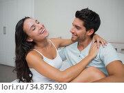 Attractive boyfriend and girlfriend laugh and cuddle in bed. Стоковое фото, агентство Wavebreak Media / Фотобанк Лори