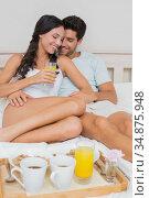 Attractive couple cuddle while having breakfast in bed. Стоковое фото, агентство Wavebreak Media / Фотобанк Лори