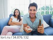 Handsome man enjoying the tv without his girlfriend. Стоковое фото, агентство Wavebreak Media / Фотобанк Лори