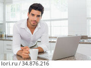 Attractive man working on laptop and looking into camera. Стоковое фото, агентство Wavebreak Media / Фотобанк Лори