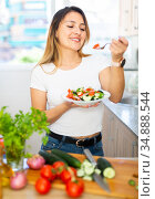 Young female holding plate of fresh vegetable salad at kitchen. Стоковое фото, фотограф Яков Филимонов / Фотобанк Лори