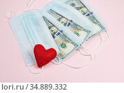 Red heart,medical masks and dollars on pink.Helping poor countries with money and masks.Financial crisis due to coronavirus.Cash payments to doctors.Expensive hospital services. Medical research. Стоковое фото, фотограф Papoyan Irina / Фотобанк Лори