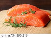 Raw salmon fillet with rosemary on wooden cutting board. Стоковое фото, фотограф Olena Mykhaylova / easy Fotostock / Фотобанк Лори