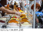 Saratov, Russia - 10/04/2020: Sale of various natural fragrant Asian Indian spices in bags in an oriental bazaar, a man's hand in a glove offers sells goods in a scoop to a woman buyer. Редакционное фото, фотограф Светлана Евграфова / Фотобанк Лори
