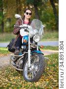 Female motorcycle rider sitting on a classic motorbike, woman with helmet in hands. Portrait in autumn park. Стоковое фото, фотограф Кекяляйнен Андрей / Фотобанк Лори