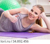 Young woman exercising with stability ball in gym. Стоковое фото, фотограф Elnur / Фотобанк Лори