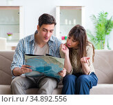 Young family discussing travel plans with map. Стоковое фото, фотограф Elnur / Фотобанк Лори