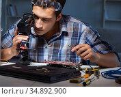 Repairman trying to repair laptop with miscroscope. Стоковое фото, фотограф Elnur / Фотобанк Лори