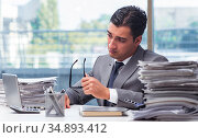 Busy angry businessman with heaps of paper. Стоковое фото, фотограф Elnur / Фотобанк Лори