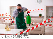 Young male sanitizer disinfecting indoors. Стоковое фото, фотограф Elnur / Фотобанк Лори