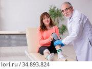 Young leg injured woman visiting old doctor traumatologist. Стоковое фото, фотограф Elnur / Фотобанк Лори