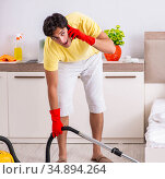 Young handsome man cleaning in the bedroom. Стоковое фото, фотограф Elnur / Фотобанк Лори